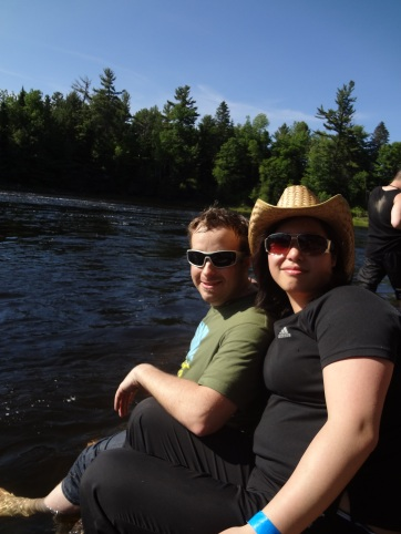 Friends with awesome hat and shades relaxing near the water
