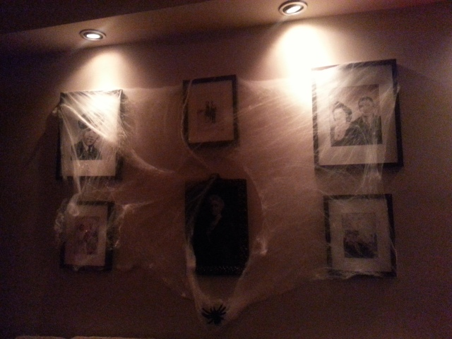 Spider web covered walls with creepy photos